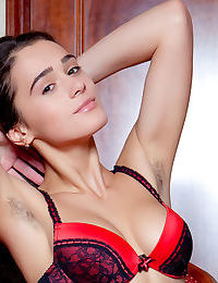 Pretty Penelope in lingerie & red stockings undressing to show her young body