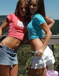 Teen lesbians remove their skirts to pose together in thong underwear
